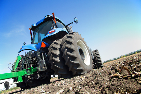 technologically: Tractor working on the farm, a modern agricultural transport, a farmer working in the field, preparing the land for planting, tractor on the background of blue sky, working plowed field