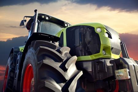 agricultura: Alimentador que trabaja en la granja, un transporte agrícola moderna, un granjero que trabajaba en el campo, tractor al atardecer, un tractor moderno de cerca