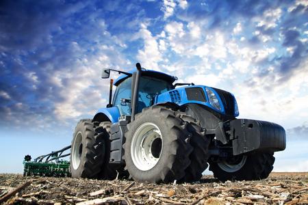 Las ruedas del tractor en el campo enorme, un granjero monta un tractor, un tractor trabajando en un campo de la maquinaria agrícola en el trabajo, un tractor en el fondo del cielo nublado