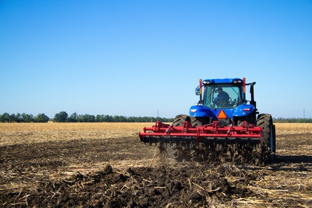 technologically: Tractor with plow working on the farm, a modern agricultural transport, a farmer working in the field, preparing the land for planting, tractor on the background of blue sky, working plowed field