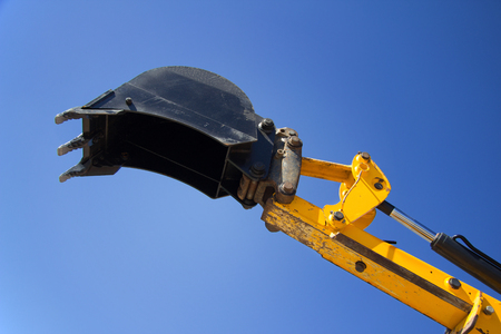 construction machinery: Shovel bucket against the blue sky, lift loads, construction machinery, construction machinery manipulator, unloading cargo, hydraulic capture truck, farm equipment, heavy tractor yellow.