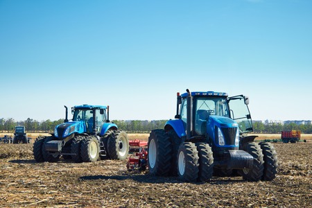 technologically: Modern agricultural machinery, tractors under a blue sky, agricultural machines, cultivation of the soil on the farm, a tractor working in a field, agricultural machinery in the work