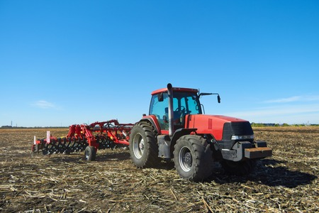 technologically: Tractor with plow working on the farm, a modern agricultural transport, tractor working in the field, preparing the land for planting, tractor on the background of blue sky, working plowed field