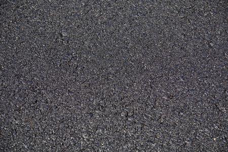 The texture of the new asphalt, pavement bitumen coating, the surface of the road, close-up shot of the asphalt coating, horizontal road surface texture. Stock Photo