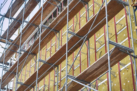 resource conservation: Wall insulation, mineral wool, resource conservation, scaffolding, carrying out aerial work, insulation of facades, building material, building facing work. Stock Photo