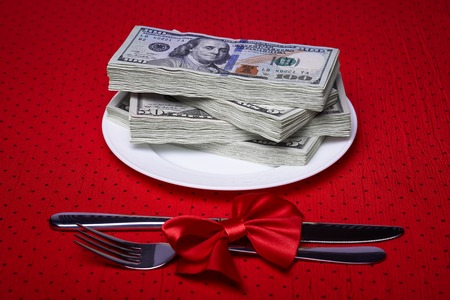 pack of dollars: Pack of dollars on a plate, cutlery on the tablecloth, red bow of the braid, economic concept, serving business lunch, a red tablecloth in a black polka dots.