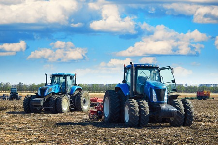 agricultural farm land: Modern agricultural machinery, tractors under a cloudy sky, agricultural machines, cultivation of the soil on the farm, a tractor working in a field, agricultural machinery in the work Stock Photo