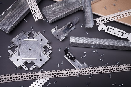 making hole: Profile for plasterboard, gypsum board, plasterboard fastening, set of building profiles, building materials, steel profiles for repair, construction works, screws for construction, plastic profile Stock Photo