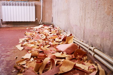 wiped out: Carrying out repair work, the replacement of old paper wallpaper, renovation of residential apartments, wiped flooring, heating system, heating radiator, construction debris, concrete wall. Stock Photo