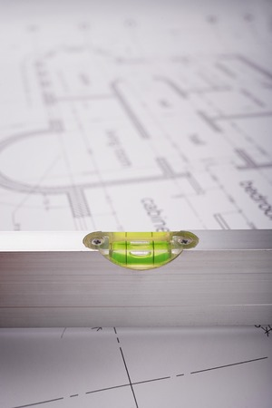 bubble level: Bubble level, measuring tool, construction of the building layout, building drawing on paper, quality control of construction works Stock Photo