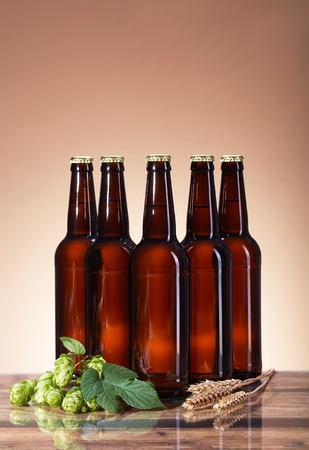 highlight: Assortment of fresh beer in bottles, ears of wheat, ripe fruit hops brewing ingredients, glass beverage bottle, a wooden table