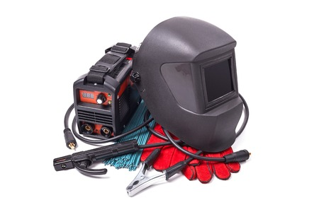Inverter welding machine, welding equipment, isolated on a white background, welding mask, leather gloves, welding electrodes, high-voltage wires with clips, set of accessories for arc welding Stock Photo