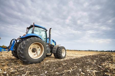 arando: Tractor trabajando en un campo, maquinaria agrícola en el trabajo, un tractor en el fondo del cielo nublado