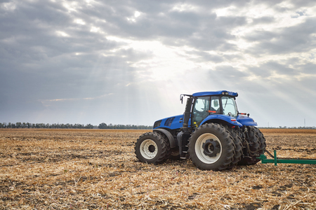 the arable land: Tractor working in a field, agricultural machinery in the work, tractor in the background cloudy sky
