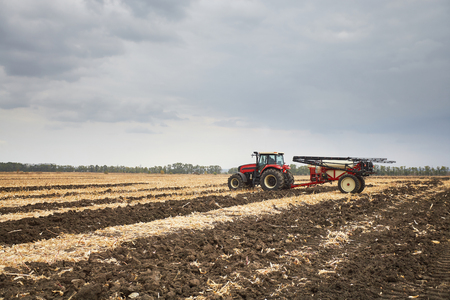 Farmer riding a tractor, a tractor working in a field, agricultural machinery in the work, tractor in the background cloudy sky Stock Photo