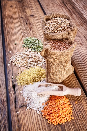 Krupa scoop, wooden spoon, an assortment of cereals, a table of old wood, the grain harvest, organic food, a bag of barley, texture of old wood, kitchen utensils, health food, scattering grains Stock Photo