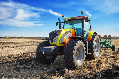 Tractor working in a field, agricultural machinery in the work, machine cultivates the land, tractor in the background cloudy sky Stock Photo