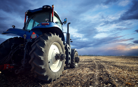 Tractor working on the farm, a modern agricultural transport, a farmer working in the field, tractor at sunset, fertile land, modern tractor closeup, cultivation of land
