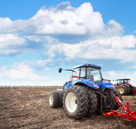 Tractor working on the farm, a modern agricultural transport, a farmer working in the field, fertile land, tractor on cloudy sky background, cultivation of land, agricultural machine