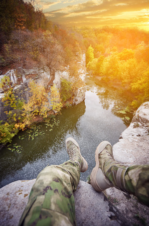 Traveler at a mountain river, legs over a cliff, outdoor clothing, deep stone canyon, ancient granite rocks, beautiful sunset, rocky river bank, cloudy sky, mountain landscape, forest on the riverbank