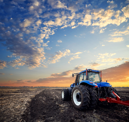 Tractor working on the farm, a modern agricultural transport, a farmer working in the field, fertile land, tractor on a sunset background, cultivation of land, agricultural machine Stock Photo