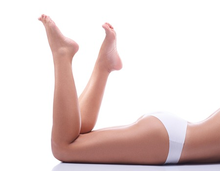 The legs of a young girl, part of the female body, tanned skin, body care, female legs isolated on white background, healthy and clean skin, health care, girl in underwear, french pedicure.