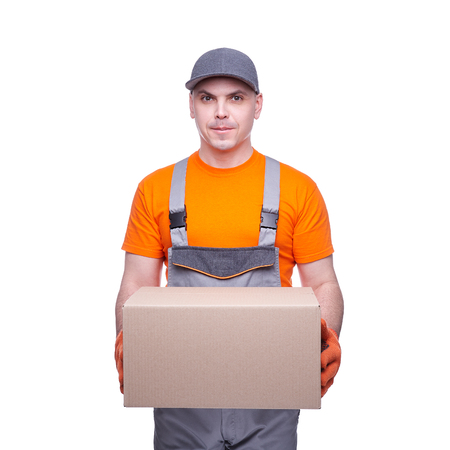 Loader in workwear, profession of the service industry, cardboard box, parcel delivery, young sports man, cargo transportation, courier in working clothes, worker isolated on white background Standard-Bild - 117343099