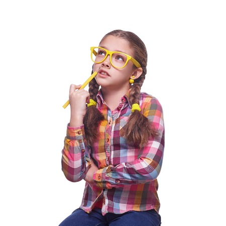 Teenager with a pencil, a girl writes, childrens emotions, schoolgirl doing homework, girl with glasses, home clothes, portrait of a young girl, isolated on white background Stock fotó