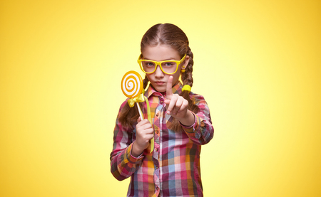 Little girl with candy, baby eating lollipop, childrens emotions, girl with glasses, bright checkered shirt, portrait of a young girl