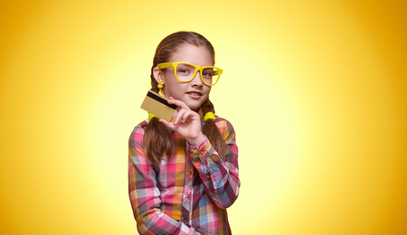 Teenager with a credit card, pensive mood, childrens emotions, girl with glasses, bright checkered shirt, portrait of a young girl