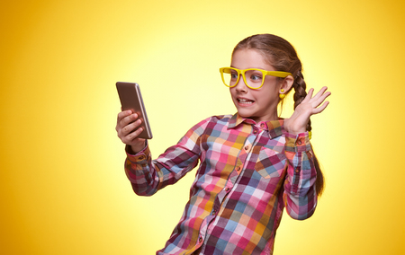 Emotional teenager, the little girl plays with the phone, childrens emotions, girl with glasses, bright checkered shirt, portrait of a young girl