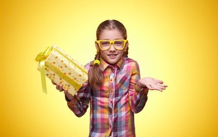 Teenager with a gift, disappointed expression, childrens emotions, girl with glasses, bright checkered shirt, portrait of a young girl
