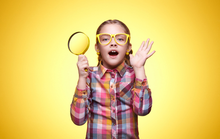 Teenager with a magnifying glass, playful mood, childrens emotions, girl with glasses, bright checkered shirt, portrait of a young girl