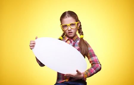 Teenager girl with a poster for text, cheeky facial expression, childrens emotions, girl with glasses, portrait of a young girl
