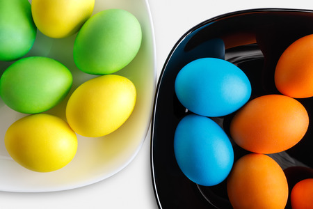 Colorful easter eggs on a black and white plates. photo