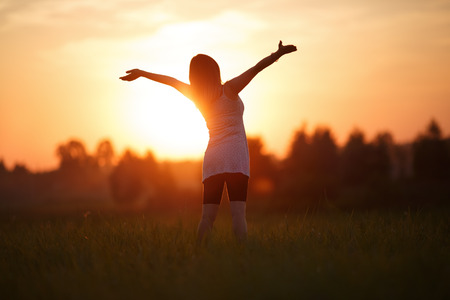 Girl with arms raised looking at the sun. Focus on model. Shallow depth of field. photo