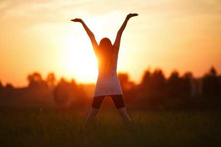 Girl with hands up on sunset background. Focus on model. Shallow depth of field.