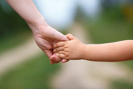 Ruce matky a dítěte. Drží se za ruce. Malá hloubka ostrosti.