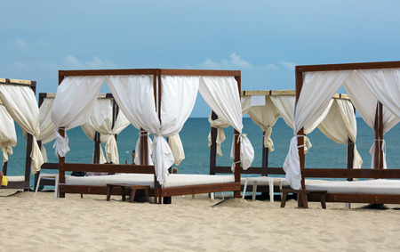Canopies with a white cloth on a background of sea and sky. Focus on the main subject of the picture. Shallow depth of field. photo