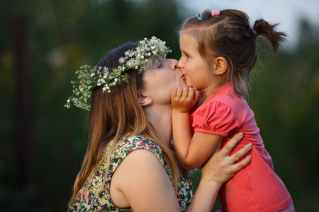 Happy mother wearing a wreath of wildflowers and daughter kissing. Sunset lighting. Shallow depth of field. Focus on models. photo