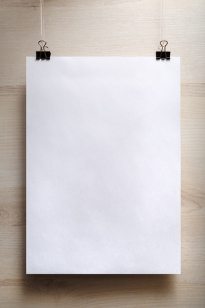 hanging: Blank white poster on a light wooden background. Vertical shot. Stock Photo