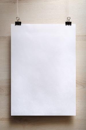 Lege witte poster op een lichte houten achtergrond. Verticaal schot.