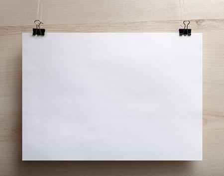 ホワイト ペーパー ポスター軽い木製の背景に掛かっています。