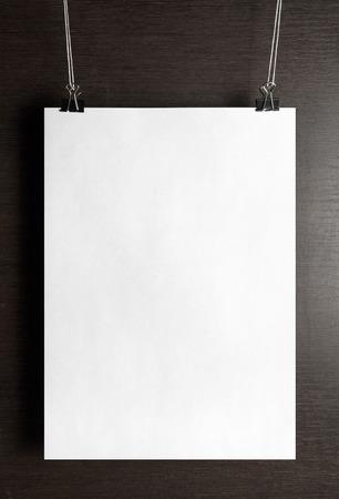 Biała kartka papieru plakat wisi na drewnianym tle. Pionowe strzału.