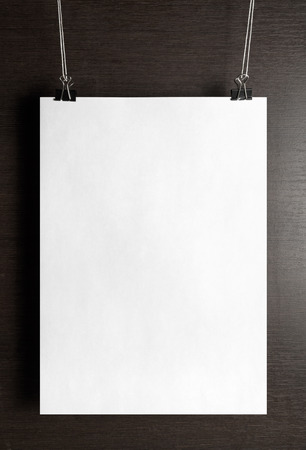 Blank white paper poster hanging on a wooden background. Vertical shot.
