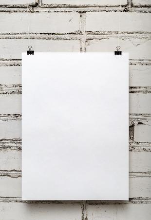 흰색 벽돌 벽에 빈 흰색 포스터. 세로 촬영.