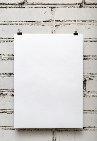 Blank white poster against a white brick wall. Vertical shot.