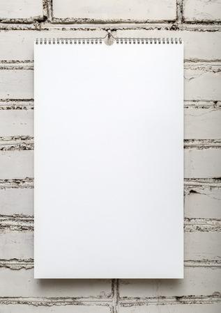 Blanco album op een veer tegen een witte bakstenen muur. Sjabloon voor het ontwerp kalenders en fotoalbums. Verticaal schot.