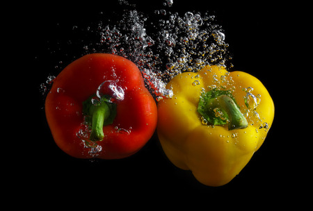 Red and yellow peppers in water with air bubbles. Photo on black background. photo