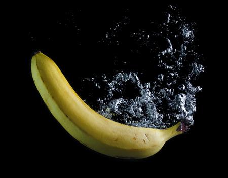 검은 배경에 바나나가 물에 떨어졌습니다. 물에 공기 방울이입니다.
